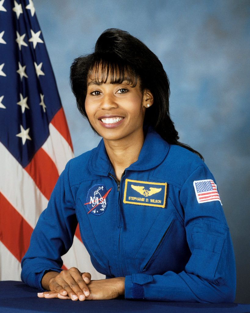 NASA Astronaut, Stephanie Wilson, posing in front of American flag
