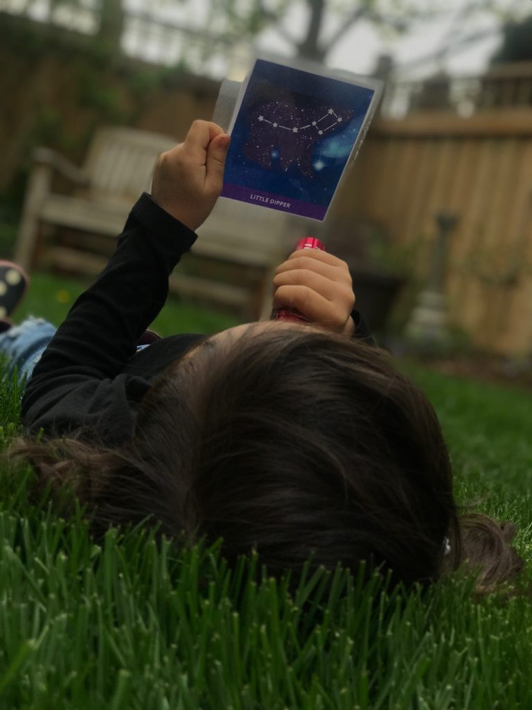 A child laying in the grass, looking up at the sky. She is holding a drawing of a constellation.